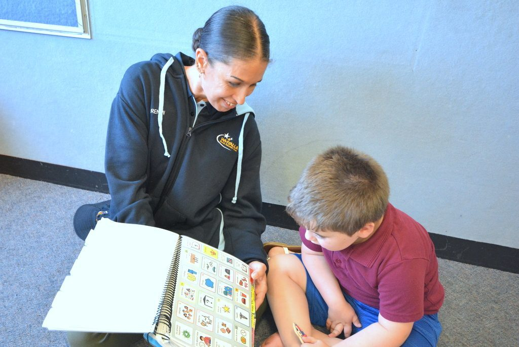 Teacher and student sitting down while looking at book